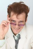 Cheerful tousled guy looks over eyeglasses Stock Photography