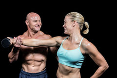 Cheerful trainer helping woman for lifting dumbbell. Cheerful trainer helping women for lifting dumbbell against black background Royalty Free Stock Photography