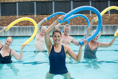 Cheerful trainer and senior swimmers exercising with pool noodle Royalty Free Stock Photography