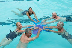 Cheerful trainers and senior swimmers in pool. High angle view of cheerful trainers and senior swimmers in pool Stock Photos