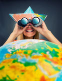Cheerful traveler girl. Discovering map with binoculars Stock Photography