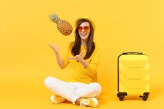 Cheerful traveler tourist woman in summer clothes, hat throw up fresh pineapple fruit isolated on yellow orange. Background. Passenger traveling abroad on stock photos