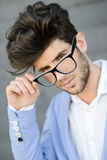 Cheerful trendy guy with black eyeglasses on Royalty Free Stock Photos