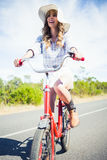 Cheerful trendy woman posing while riding bike Stock Photography