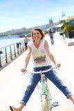 Cheerful trendy woman on a retro bike in town having fun Royalty Free Stock Photos