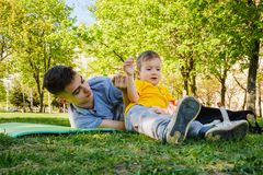 Cheerful two brothers lie on the grass in the park and play in funny games. Smiling royalty free stock images