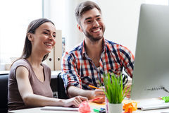 Cheerful two colleagues are using laptop for work Stock Photo