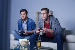 Cheerful two friends are entertaining with play-station Stock Images