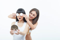 Cheerful two girls are making fun with cosmetics Royalty Free Stock Images