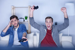 Cheerful two guys are competing in video game Royalty Free Stock Photography