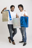 Cheerful Two happy smart young boys with shopping bags Stock Images
