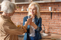 Cheerful two mature ladies drinking healthy beverage. Caring old women is giving glass of fresh juice to her friend. They are standing in kitchen and smiling royalty free stock photo