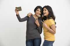 Cheerful two pretty young women taking selfie with mobile phone Royalty Free Stock Image