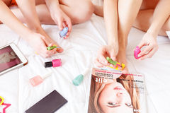 Cheerful two women painting nails on feet. Young girls making pedicure at home together. They are sitting on bed near fashionable magazine, mobile phone and Royalty Free Stock Photography