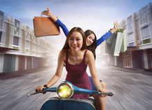 Cheerful two young asian woman with shopping bag riding a scoote. Cheerful two young asian women with shopping bag riding a scooter in town with fun Royalty Free Stock Photography