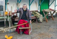 Cheerful Ukrainian peasant getting ready to whet a scythe Stock Photos