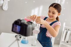 Cheerful video blogger pouring pink chemical into water. Little prodigy. Adorable pretty pre-teen girl pouring a pink chemical into the flask with water and Stock Photo