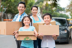 Cheerful Vietnamese family. Holding boxes and looking at the camera Royalty Free Stock Images