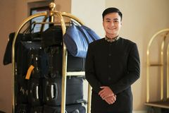Smiling porter. Cheerful Vietnamese porter and hotel baggage cart in the background royalty free stock photo