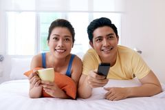 Watching tv series. Cheerful Vietnamese young couple lying in bed and watching tv series Stock Photo