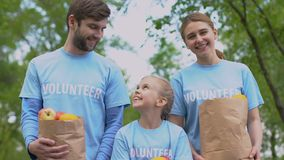Cheerful volunteers family with apples paper bags smiling on camera, charity stock footage