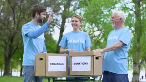 Cheerful volunteers giving high five, donation boxes on table, charity event. Stock footage stock video footage