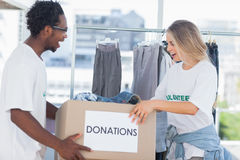 Cheerful volunteers looking at a donation box Stock Image