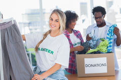 Cheerful volunteers putting clothes in clothes rail Royalty Free Stock Photography