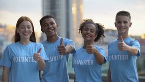 Cheerful volunteers showing thumbs up smiling camera, international support stock video