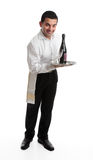 Cheerful Waiter or barman. A smiling friendly waiter, bartender, or domestic staff, holding or presenting a tray with a bottle of  wine and glasses.  White Royalty Free Stock Photography