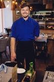 Cheerful waiter in modern restaurant Stock Photo