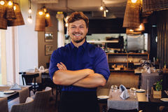 Cheerful waiter in modern restaurant.  Royalty Free Stock Photo
