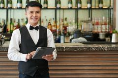 Cheerful waiter. Portrait of smiling Vietnamese waiter with digital tablet standing at bar Stock Image