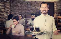 Cheerful waiter taking care of adults at cafe table. Cheerful waiter taking care of adults guest at cafe table Royalty Free Stock Images