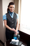 Cheerful waitress opening bottle of beverage Stock Photo