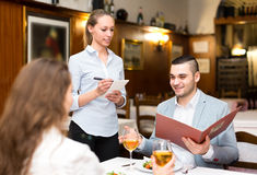 Cheerful waitress taking a table order Royalty Free Stock Images