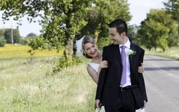 Cheerful wedding couple. Happy newlyweds couple in countryside playing aside of a road royalty free stock photo