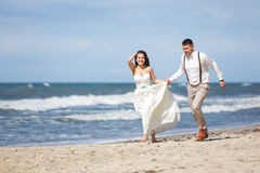 Cheerful wedding couple on the beach Stock Image