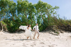 Cheerful wedding couple on the beach Royalty Free Stock Photos