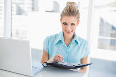 Cheerful well dressed businesswoman writing on datebook. In bright office Stock Photos