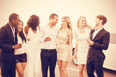 Cheerful well dressed people standing next to limousine. On night out Royalty Free Stock Photos