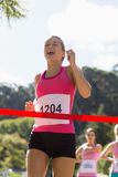 Cheerful winner athlete crossing finish line Royalty Free Stock Images