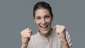 Cheerful winner woman. Cheerful excited winner woman with raised fists, she is smiling at camera Stock Photography