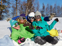 Cheerful winter vacations. Portrait of four laughing teenagers in ski goggles sitting on snow Royalty Free Stock Photo