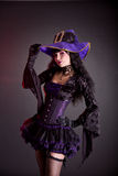 Cheerful witch in purple and black gothic Halloween costume. Cheerful witch in purple and black gothic fantasy Halloween costume, studio shot on black background Stock Photos