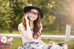 Cheerful woman alking on cell phone and using laptop outdoors. Cheerful young woman in hat and glasses talking on cell phone and using laptop outdoors Stock Photography