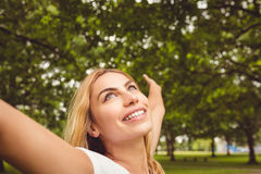 Cheerful woman with arms raised in park Royalty Free Stock Images