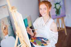 Cheerful woman artist standing and painting picture in workshop stock image
