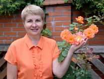 The cheerful woman of average years shows a rose hand in a garden Stock Image