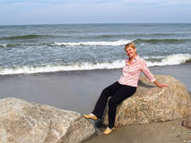 The cheerful woman of average years sits on a boulder. Coast of the Baltic Sea.  Royalty Free Stock Image